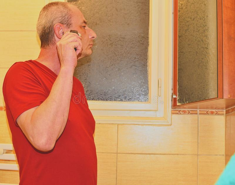 Het midden oude mens scheren in een badkamers, die scheerapparaat met behulp van Hoger concept Rijpe mens thuis stock foto