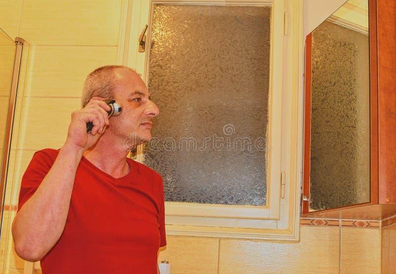 Het midden oude mens scheren in een badkamers, die scheerapparaat met behulp van Hoger concept Rijpe mens thuis stock afbeelding