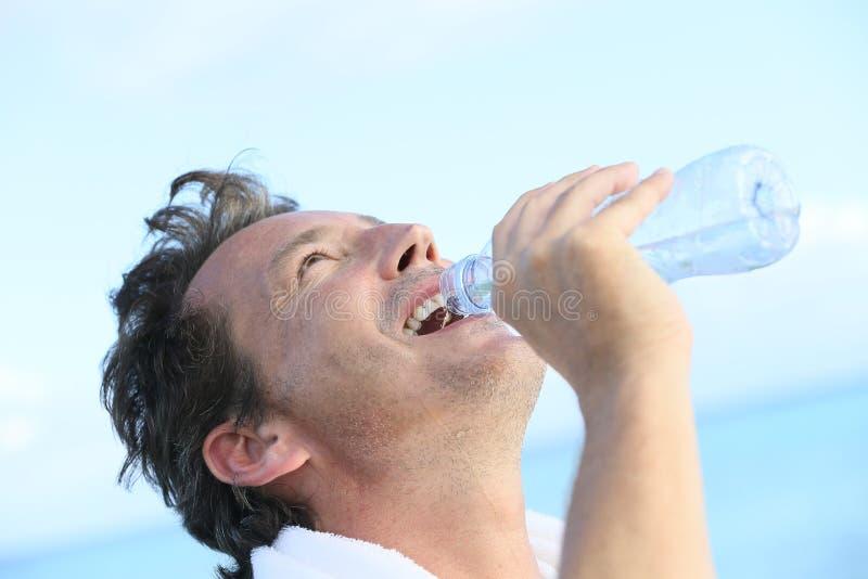 Het midden oude mensen drinkwater na werkt uit royalty-vrije stock foto