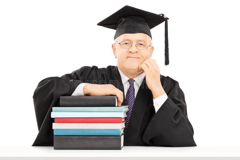 Het midden oude universiteitsprofessor stellen met een stapel boeken stock foto's