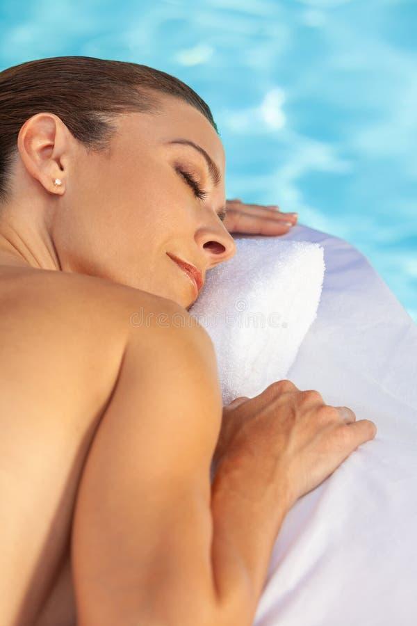 Het midden Oude Vrouw Ontspannen die door Zwembad zonnebaden stock afbeelding