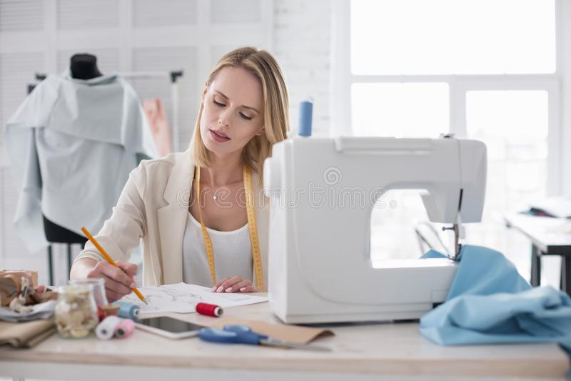 Het mijmeren van het vrouwelijke meer couturier werken aan schetsen stock foto