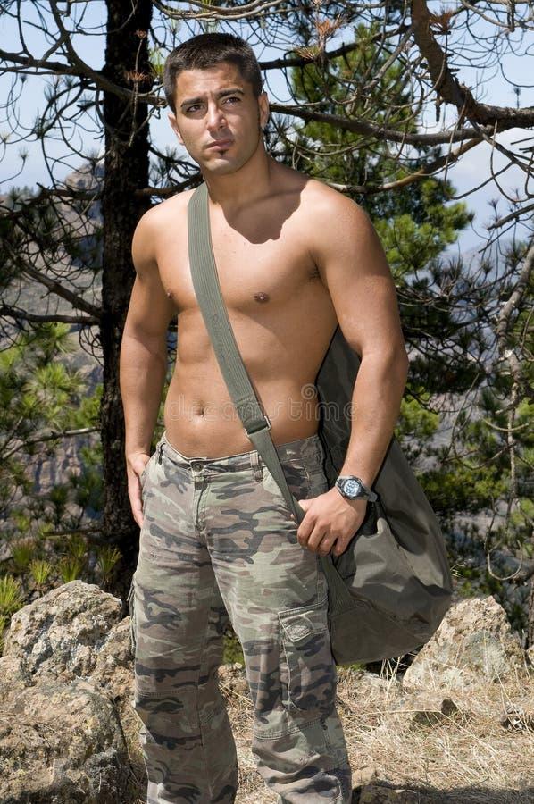 Het militaire mens ontspannen zonder overhemd stock foto