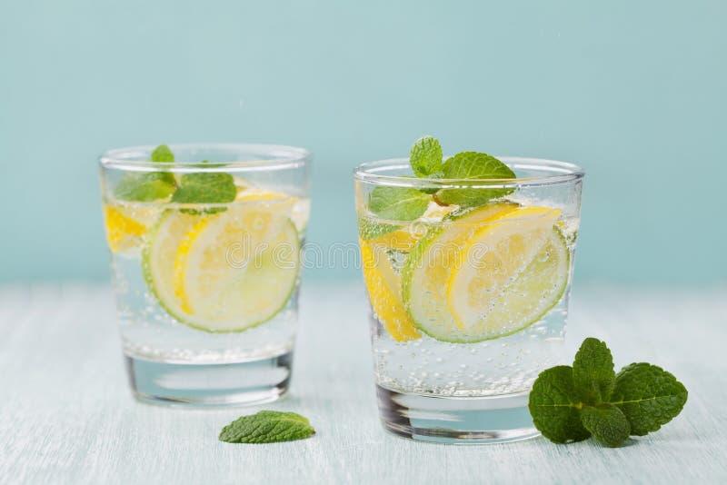 Het mineraal goot water met kalk, citroenen, ijs en muntbladeren op blauwe achtergrond, eigengemaakt detoxsodawater stock afbeeldingen