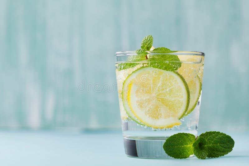 Het mineraal goot water met kalk, citroenen, ijs en muntbladeren op blauwe achtergrond, eigengemaakt detoxsodawater stock foto