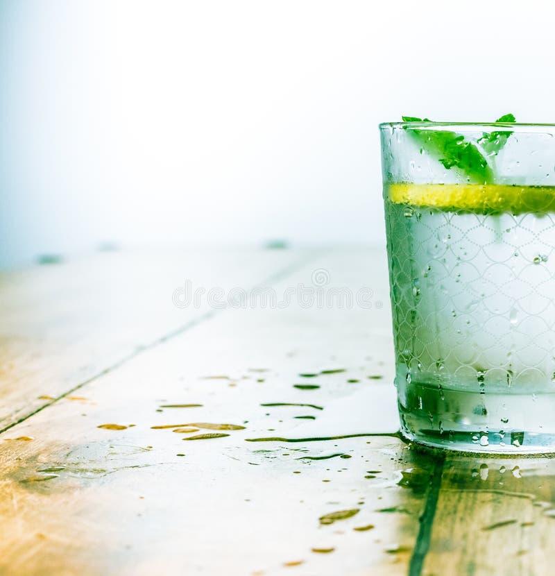 Het mineraalwater goot met kalk, citroenen, ijs en muntbladeren op witte achtergrond, het eigengemaakte recept van het detoxsodaw royalty-vrije stock afbeelding