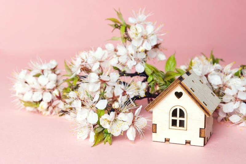 Het miniatuur houten stuk speelgoed huis met kers komt takken op roze tot bloei stock afbeeldingen
