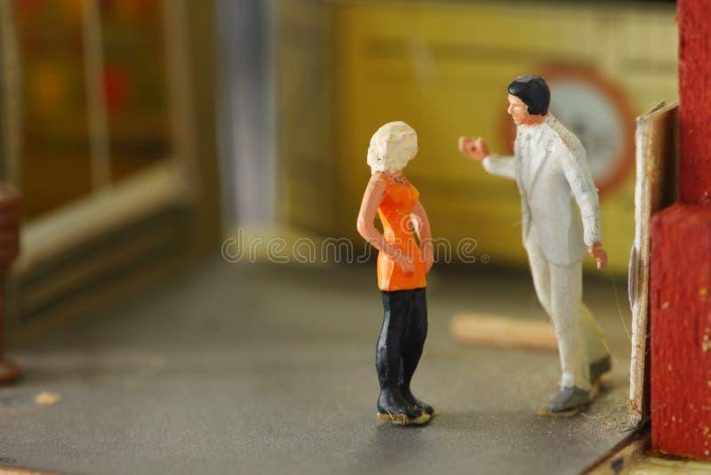 Het miniatuurcijfer plastic modelstuk speelgoed van de mens en de vrouw zetten op modelstad royalty-vrije stock fotografie