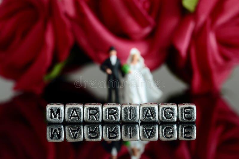 Het miniatuurpaar van het schaal modelhuwelijk met het woordhuwelijk op parels en nam boeket toe royalty-vrije stock foto's