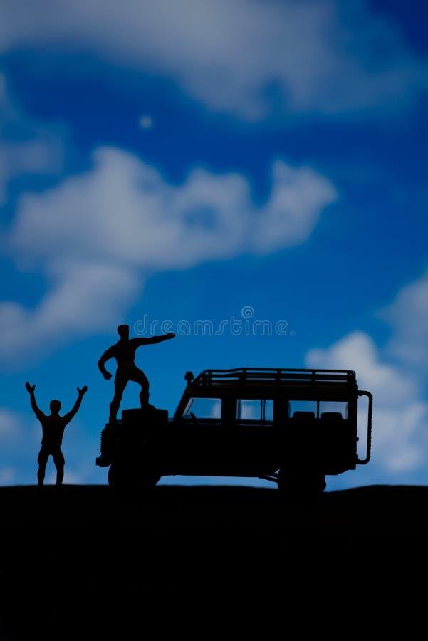 Het miniatuurspeelgoed van twee mensen viert triomfantelijk bij het bergconcept stock afbeelding