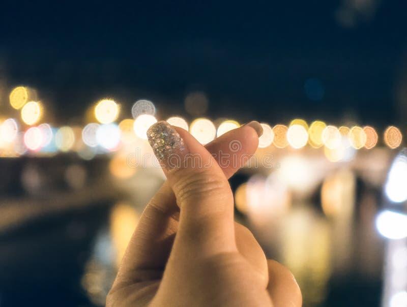 Het minihart van het vingerteken op vaag bokeh stock foto