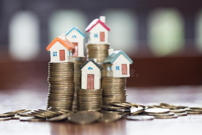Het minihuis op stapel muntstukken, Onroerende goederen Geld en huis, investeert stock foto