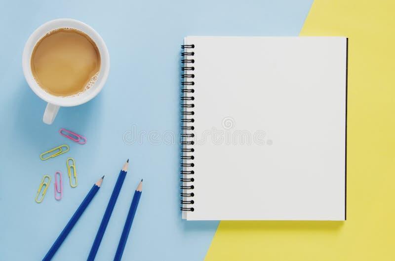 Het minimale concept van de bureauwerkplaats Leeg notitieboekje, kop van koffie, potlood, paperclip op gele en blauwe achtergrond stock foto's