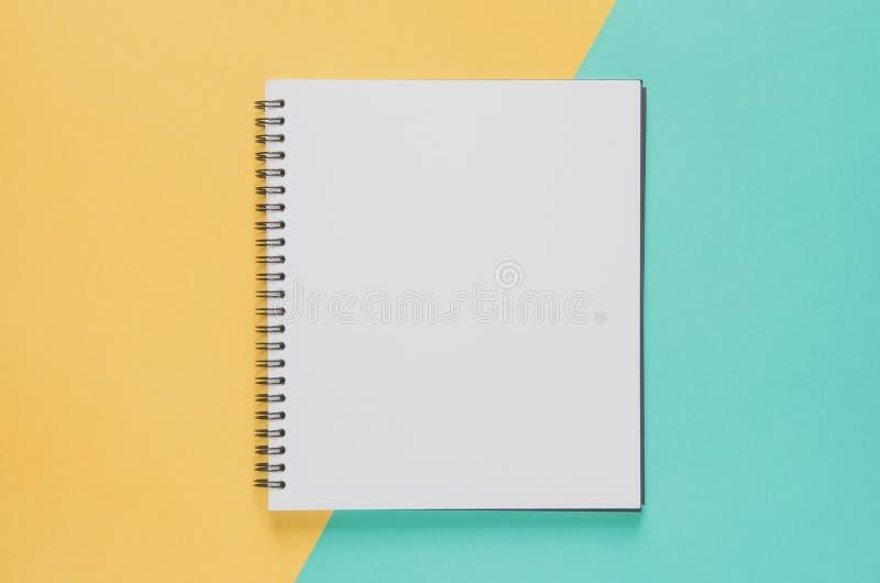 Het minimale concept van de bureauwerkplaats Leeg notitieboekje op geel en B stock foto's
