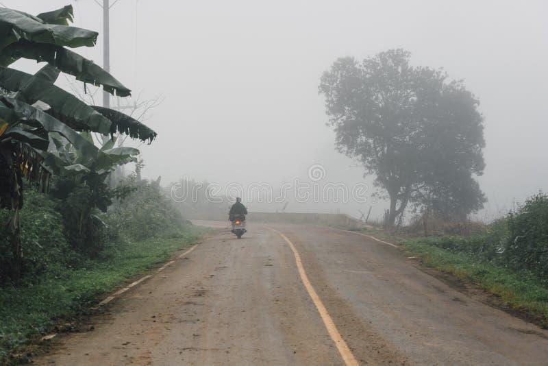 Het mistige landelijke perspectief van de asfaltweg met witte lijn, nevelige weg, Weg met verkeer en zware mist royalty-vrije stock afbeelding