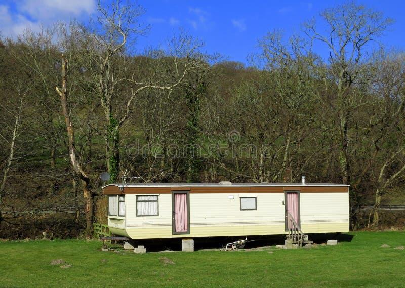 Het mobiele gesloten de aanhangwagenhuis van het vakantiehuis, verlaten, curtained, in zonlicht royalty-vrije stock fotografie
