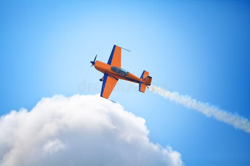 Het Mochishchevliegveld, lokale lucht toont, geel Extra EX 360 sportenvliegtuig op blauwe hemel en de witte wolkenachtergrond, sl royalty-vrije stock afbeelding