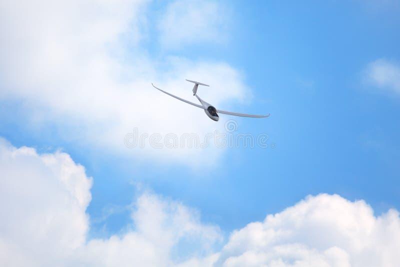 Het Mochishchevliegveld, lokale lucht toont, zweefvliegtuigvliegtuig zonder motorvliegen in de blauwe hemel met witte wolken stock afbeelding