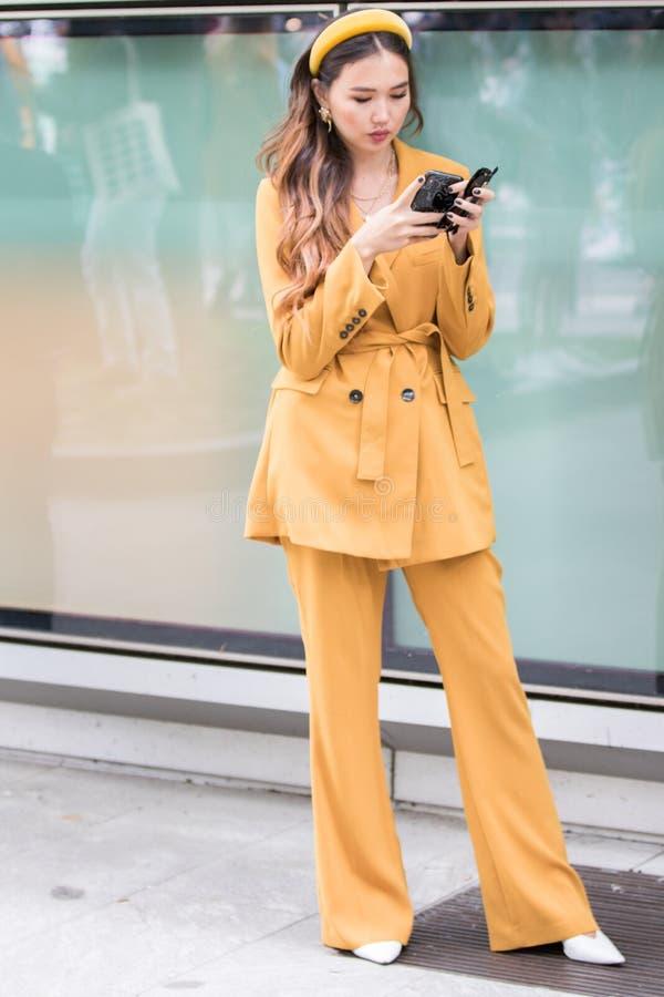 Het model draagt een oranje broek en een oranje jas, evenals een oranje haarband stock fotografie