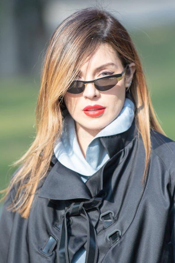 Het model draagt een zwarte overjas en een paar zonnebril stock fotografie