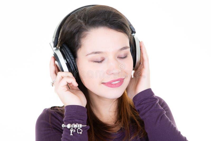 Het model jonge in mooie meisje met natuurlijke samenstelling met hoofdtelefoons sloot ogen op witte achtergrond stock fotografie
