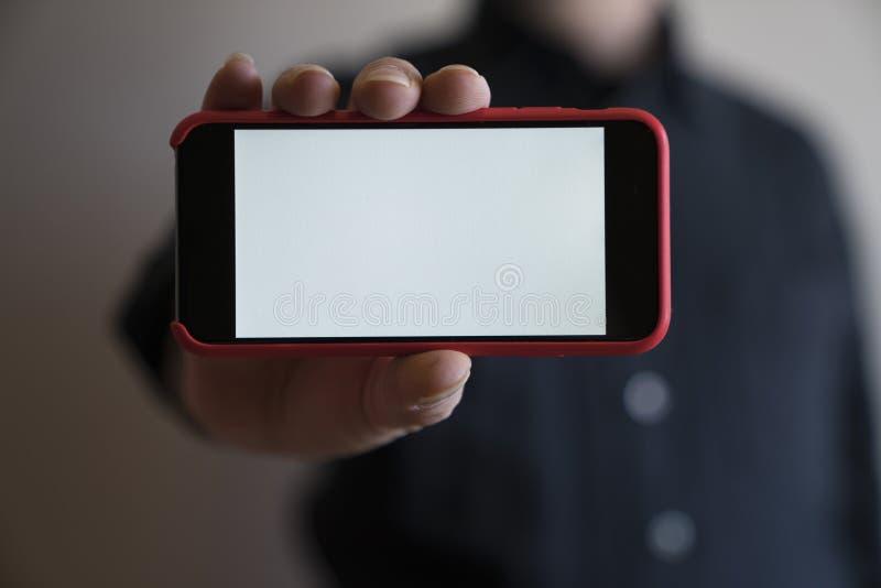 Het model overhandigt de spot van de rode kleurentelefoon op blan de vertoning van de het schermholding stock foto