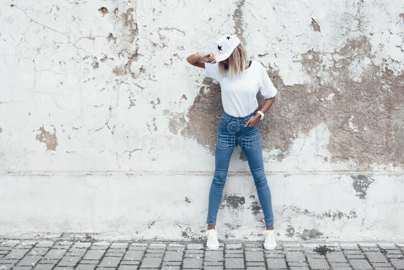 Het model stellen in duidelijke t-shirt tegen straatmuur royalty-vrije stock fotografie