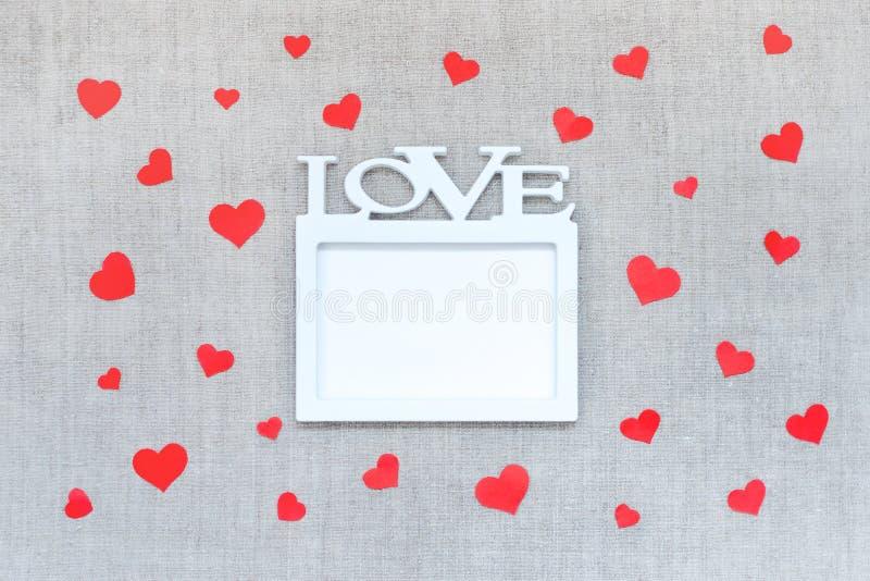 Het model van de valentijnskaartendag met wit kader met woordliefde en vele rode harten op de achtergrond van de linnenstof Valen stock afbeelding
