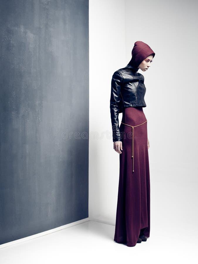 Het model stellen van de vrouw zeer dramatisch in een minimale studioopstelling stock afbeelding