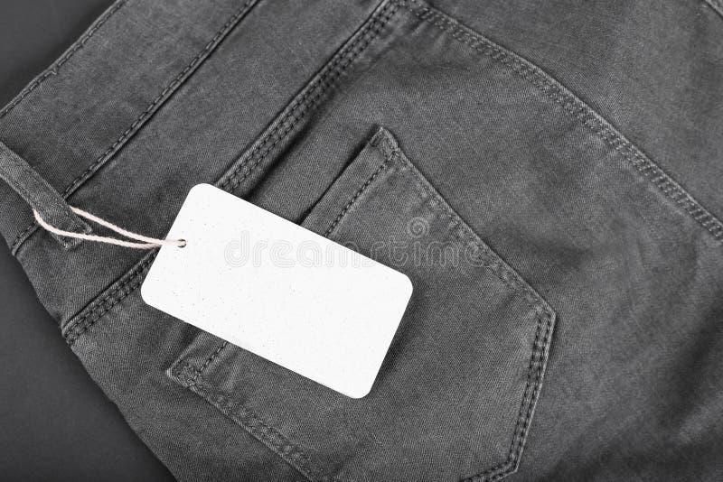 Het model van het etiketprijskaartje op zwarte jeans op zwarte achtergrond stock fotografie