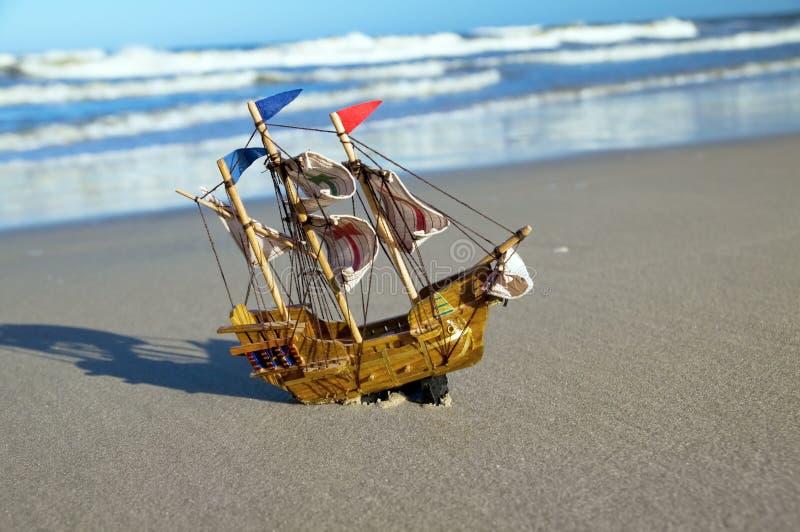 Het model van het schip op de zomer zonnig strand stock fotografie