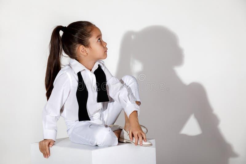 Het model van het maniermeisje in een witte kostuum en een vlinderdas royalty-vrije stock afbeeldingen