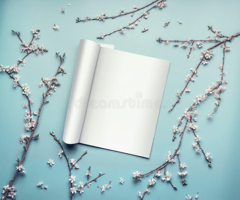Het model van open tijdschrift of catalogus op pastelkleur blauwe Desktop met takjes en de kers komen tot bloei stock fotografie