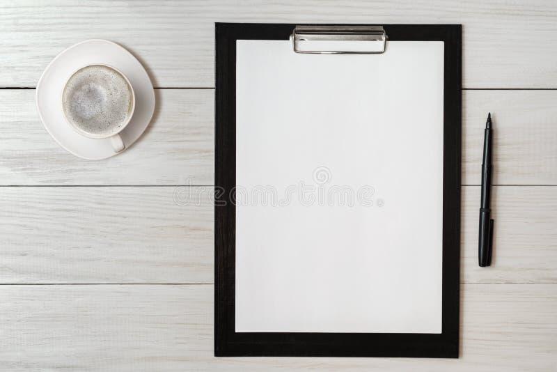 Het model voor controlelijst, het lege notadocument met pen en de koffie vormen op houten achtergrond tot een kom Bureau, schrijv stock fotografie