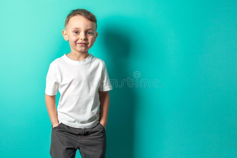 Het modelkind stellen op turkooise achtergrond stock foto's
