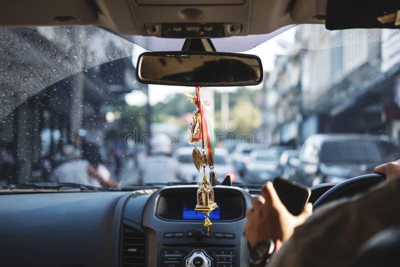 Het moderne autobinnenland met het hangen van amuletten charmeert op achteruitkijkspiegel, die op de weg, selectieve nadruk drijv stock foto's
