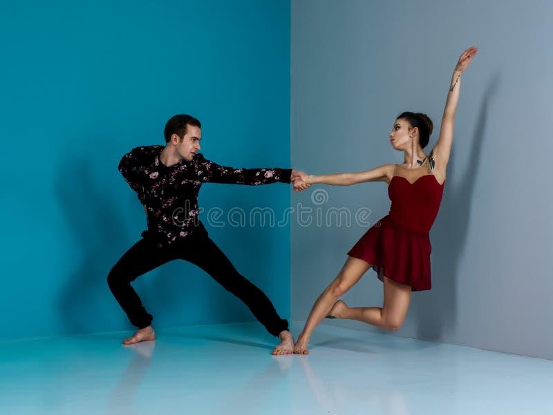Het moderne balletdanserpaar in zwarte broekenzwarte in rozenoverhemd en bordo kleden het element van de uitvoerende kunstdans me royalty-vrije stock fotografie