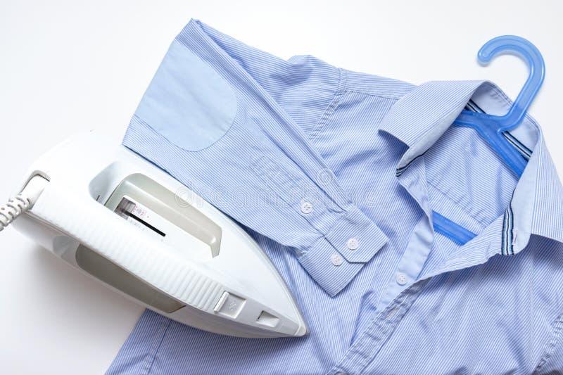 Het moderne elektrische ijzer en een blauw overhemd op witte achtergrond, wasserij en het strijken kleden concept royalty-vrije stock fotografie