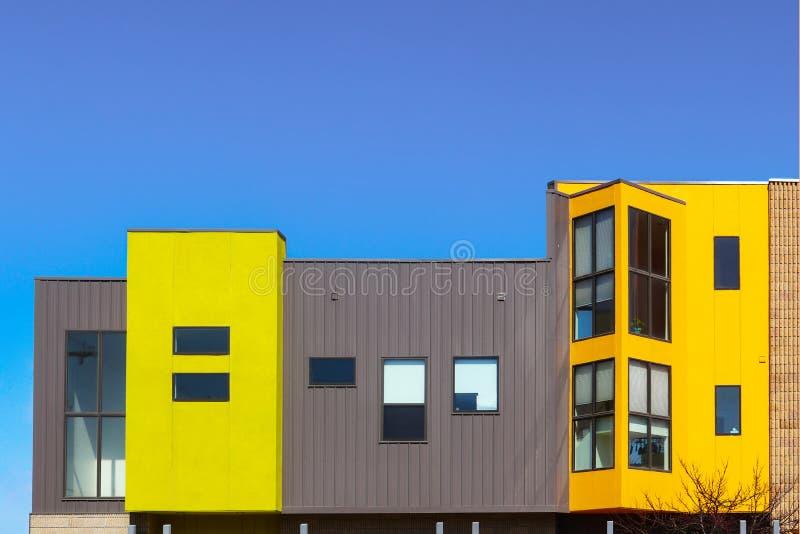 Het moderne flat of bureau builing met schone lijnen en heldere gekleurde en metaal het opruimen blokken tegen zeer blauwe hemel stock afbeeldingen