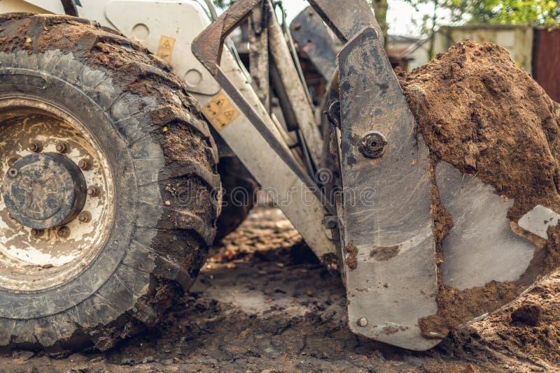 Het moderne graafwerktuig voert het uitgravingswerk aangaande de bouwwerf uit Mening over het grote vuile wiel van backhoe en  stock foto