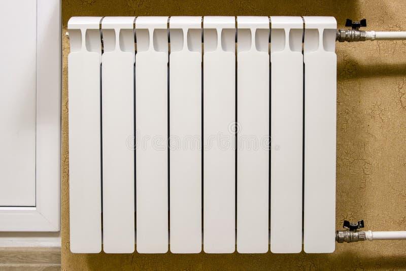 Het moderne huis witte radiator verwarmen Vervanging, reparatie, installatie van radiators, close-upfoto stock foto