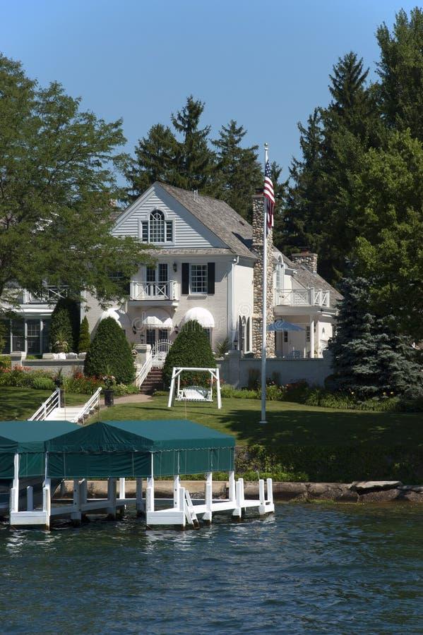 Het moderne Mooie Landgoed van de Luxe van het Huis van het Meer op Water stock afbeeldingen