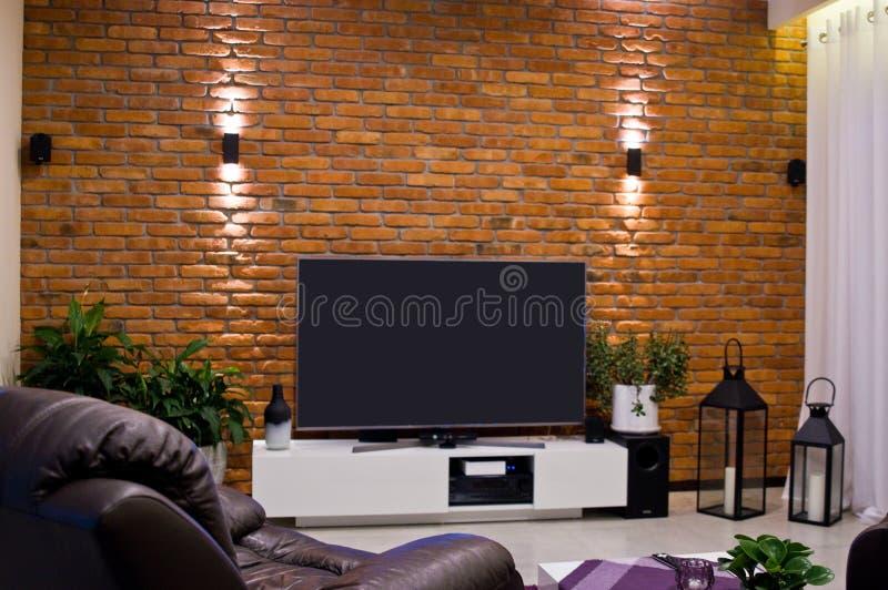Het moderne ontwerp van de huisruimte met rode bakstenen muur en vlak geleide televisie stock fotografie