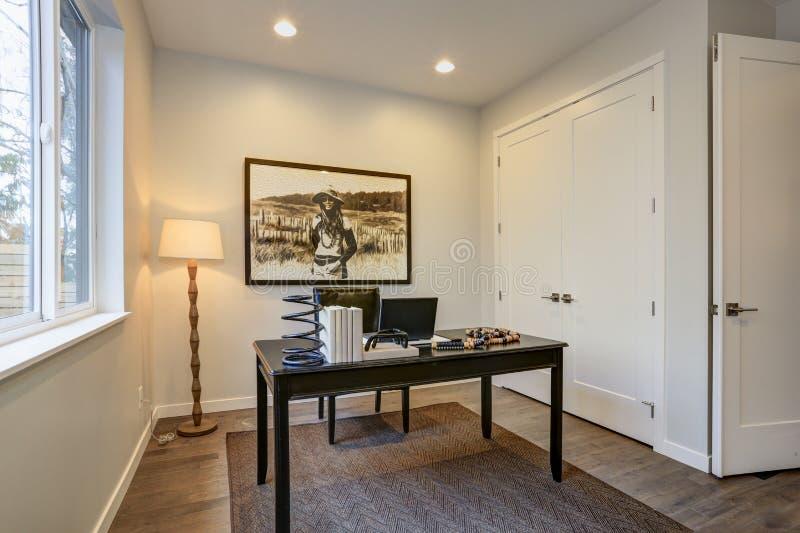 Het moderne ontwerp van het huisbureau met zwarte houten lijst stock fotografie