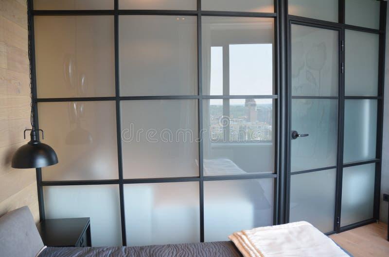 Het moderne slaapkamer in zones onderver*delen met glasmuur Modern slaapkamerbinnenland met comfortabele glasmuur en deur royalty-vrije stock fotografie