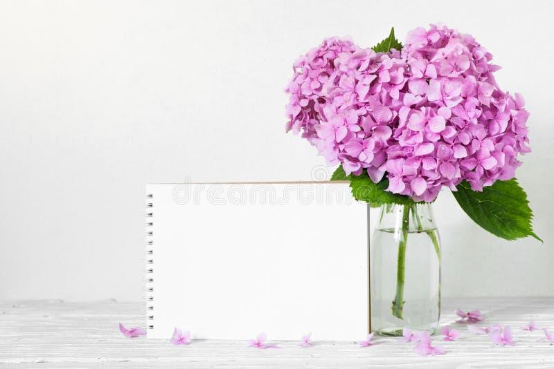 Het moderne stilleven met een mooie roze hydrangea hortensia bloeit en lege document kaart op witte houten lijst stock afbeeldingen