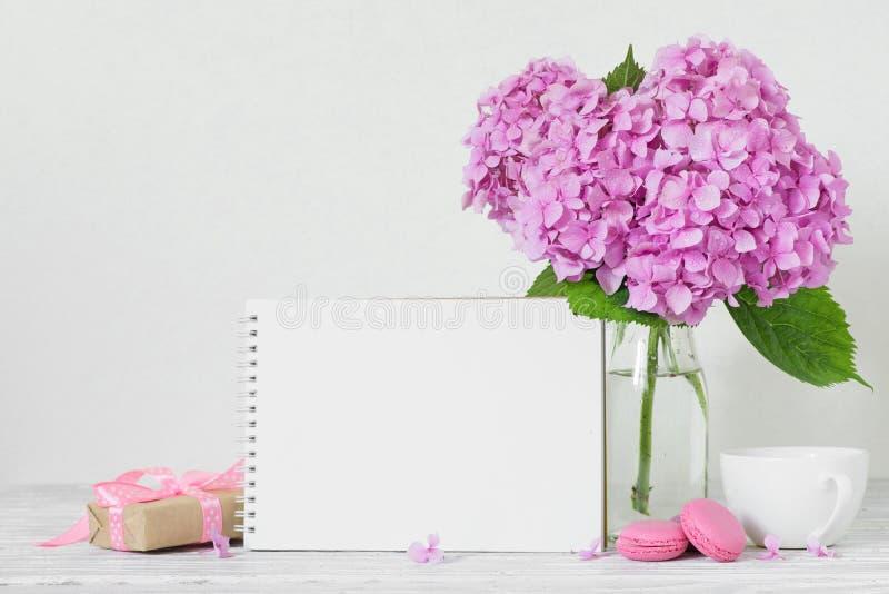 Het moderne stilleven met roze hydrangea hortensia bloeit, lege document kaart, koffiekop en giftvakje op witte houten tabl royalty-vrije stock afbeelding