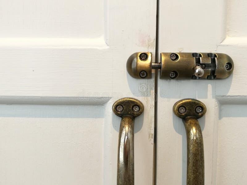 Het moderne uitstekende handvat van de stijldeur en het diaslot op witte natuurlijke houten deur, sluiten omhoog wit deur en hand stock foto