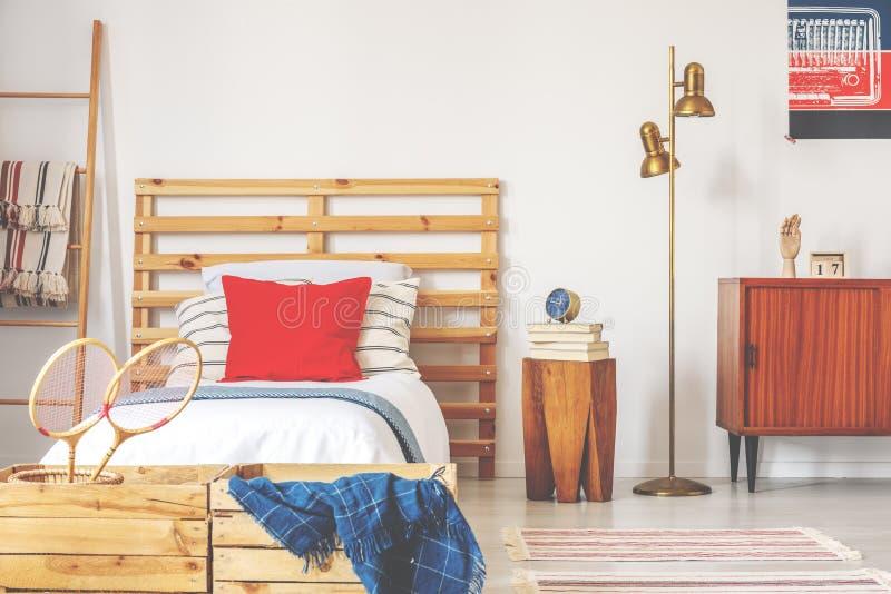 Het modieuze binnenland van de tienerslaapkamer met houten bed en uitstekend meubilair, echte foto royalty-vrije stock afbeelding