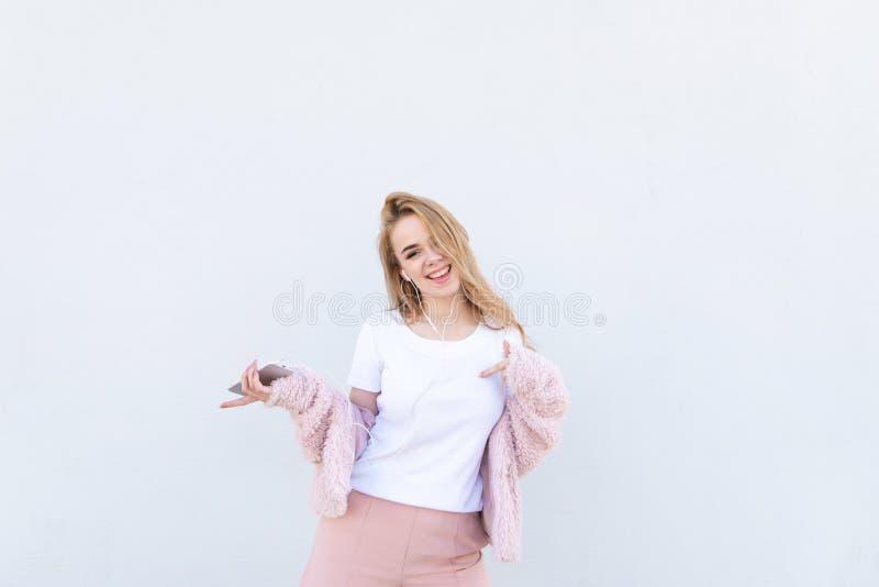 Het modieuze blondemeisje die een witte T-shirt en een roze bontjas dragen, luistert aan muziek in de hoofdtelefoons royalty-vrije stock foto's